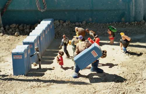 Pic of miniature portapotties with superhero figurines next to real portapotties
